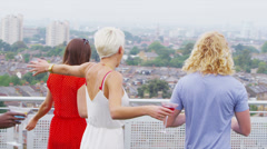 Excited friends at penthouse apartment party run out to look at view of the city - stock footage