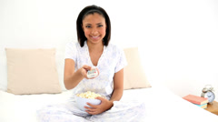 Amused young woman eating popcorn while watching television Stock Footage