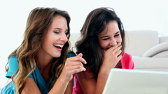 Attractive amused women using notebook lying on floor Stock Footage