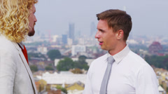 Two business men chatting on rooftop terrace with views of the city Stock Footage