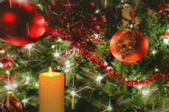 Golden candle with holiday tree decorations in background - stock footage