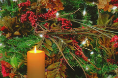 Golden candle with holiday tree decorations in background Stock Footage