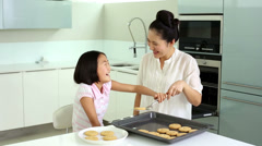 Mother and daughter taking cookies from baking tray Stock Footage