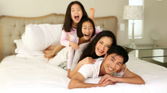Silly family playing on the bed - stock footage