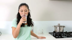 Smiling woman drinking glass of water - stock footage