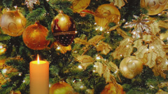 Golden candle with holiday decorations in background Stock Footage