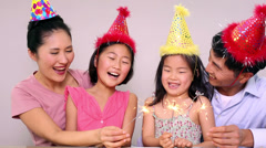 Happy family celebrating a birthday and holding sparklers - stock footage