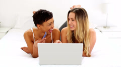 Two pretty friends shopping online lying on bed Stock Footage