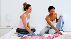 Two pretty friends jokingly fighting over clothes on bed Stock Footage