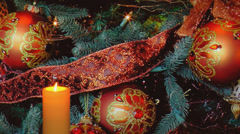 Golden candle with holiday decorations and ribbons in background Stock Footage