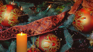 Stock Video Footage of Golden candle with holiday decorations and ribbons in background