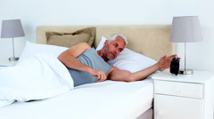 Groggy man waking up and looking at his alarm clock Stock Footage