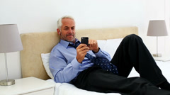 Businessman lying on his bed listening to music Stock Footage
