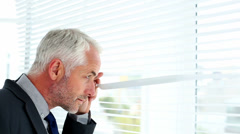 Businessman spying through blinds Stock Footage