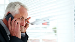 Businessman spying through blinds and reporting a crime on his phone Stock Footage