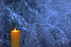 Golden candle glows with snow falling outside in the background Stock Footage