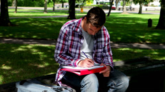 Young student studying on the bench outside Stock Footage