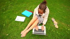 Student working with laptop sitting on grass Stock Footage