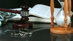 Gavel falling onto sounding block beside hourglass bible and handcuffs Stock Footage