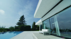 View of the exterior of a luxury contemporary home with swimming pool - stock footage