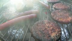 Hamburgers and hotdogs cooking and getting flipped over grill Stock Footage