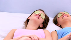 Girls lying on bed with cucumber over their eyes Stock Footage