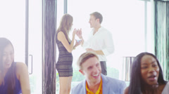 Glamorous group of young friends laughing & enjoying cocktails in modern home - stock footage