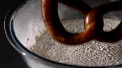 Pretzel falling into bowl of flour Stock Footage