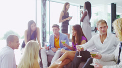 Happy group of young friends chatting over cocktails in contemporary home - stock footage