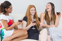 Stock Photo of Cheerful female friends with wine glasses enjoying a conversation