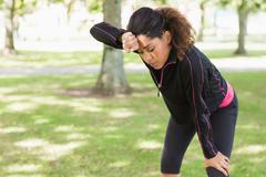 Tired woman taking a break while jogging in park Stock Photos