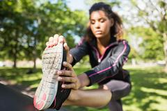Pretty sporty woman stretching her leg in park - stock photo