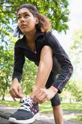 Sporty young woman wearing shoes in park - stock photo