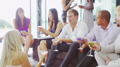 Glamorous group of young friends chatting over cocktails in luxury modern home Stock Footage