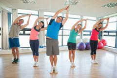 Fitness class and instructor standing in Namaste position - stock photo