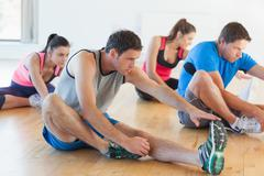 Class and instructor stretching legs in exercise room Stock Photos