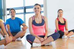 Smiling fitness class and instructor sitting on floor - stock photo