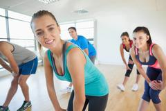 Fitness class and instructor doing power fitness exercise - stock photo
