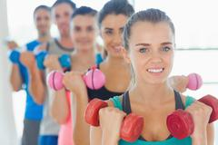 Stock Photo of People lifting dumbbell weights with trainer in gym