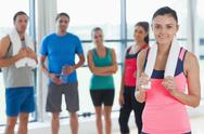 Stock Photo of Instructor with fitness class in background in fitness studio