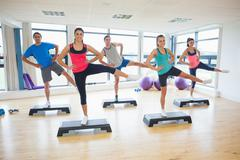 Stock Photo of Instructor with fitness class performing step aerobics exercise