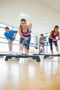 Stock Photo of Instructor with fitness class performing step aerobics exercise with dumbbells