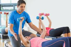 Trainer helping woman at fitness studio Stock Photos