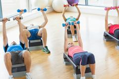 Instructor with fitness class performing step aerobics exercise with dumbbells - stock photo