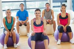 Stock Photo of Smiling people sitting on exercise balls in the bright gym
