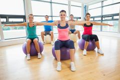 Sporty people stretching out hands on exercise balls at gym - stock photo