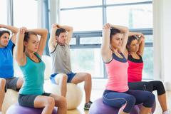 Sporty people stretching hands on exercise balls at gym - stock photo