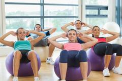 Class doing abdominal crunches on fitness balls - stock photo