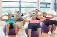 Stock Photo of Class doing abdominal crunches on fitness balls