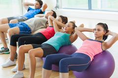 Class doing abdominal crunches on fitness balls in row - stock photo